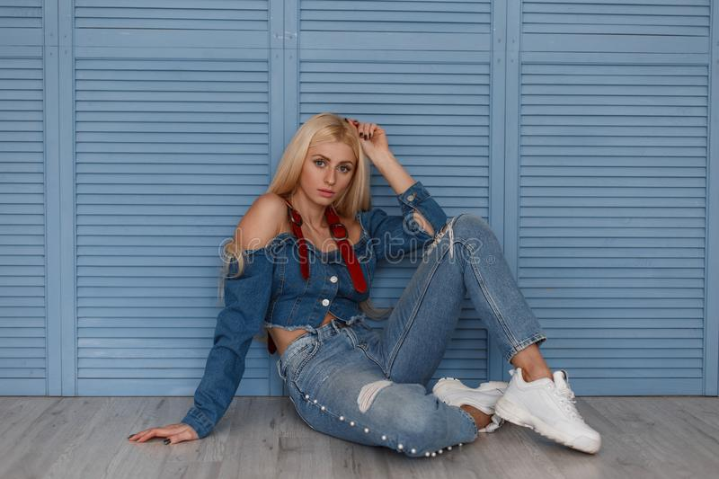 Young beautiful blond girl model in fashion denim clothes with stylish jeans and white sneakers sitting near the blue wooden wall. royalty free stock images