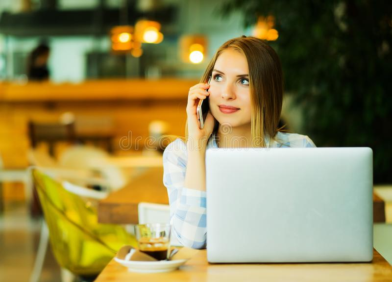 Young beautiful blond girl sitting in a coffee shop and working on computer. Image of happy woman using laptop and smartphone in cafe stock image
