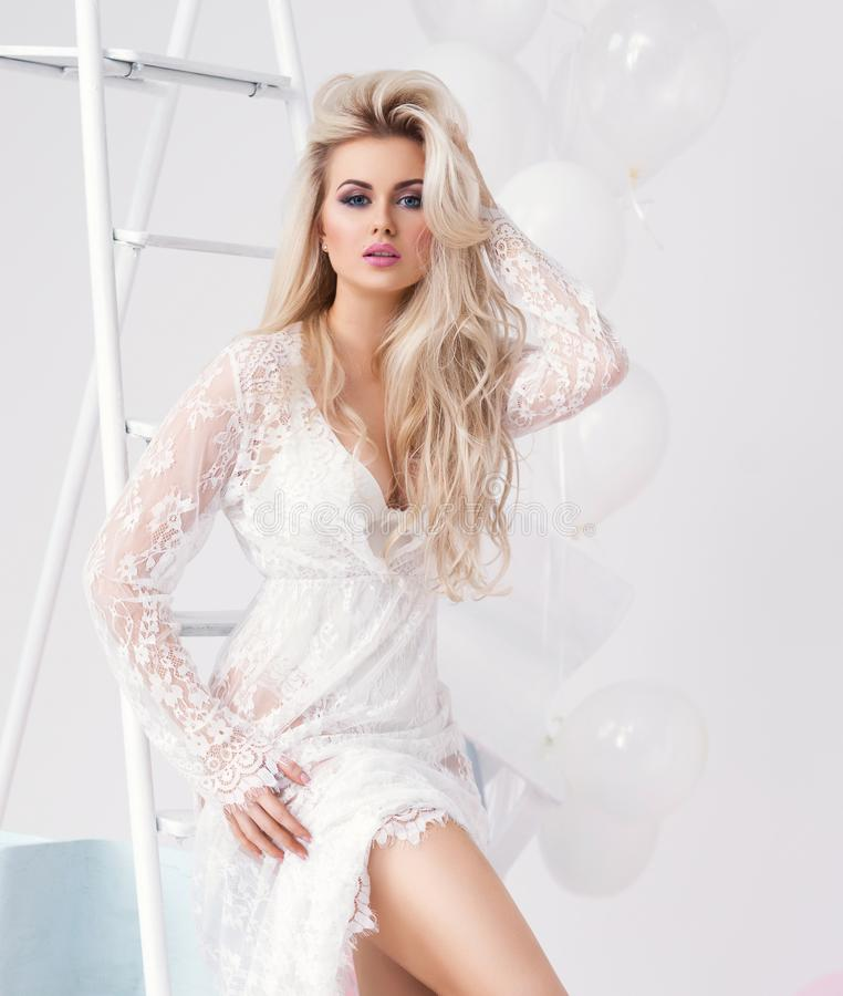 Young and beautiful blond girl in a white dress royalty free stock image