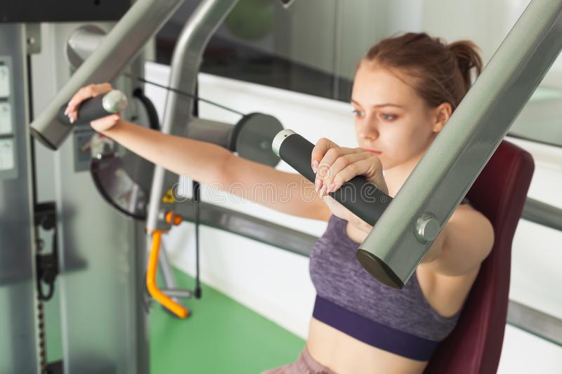 Girl does machine chest press exercising. Young beautiful blond sporty girl does machine chest press exercising in a gym stock photos