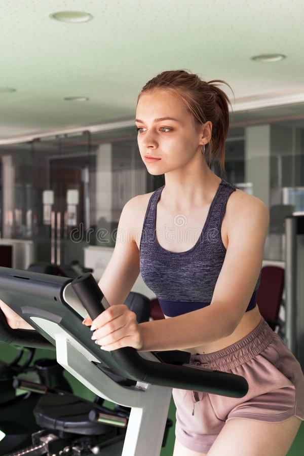 Girl is engaged on a stationary bike in a gym. Young beautiful blond sporty girl is engaged on a stationary bike in a gym stock image