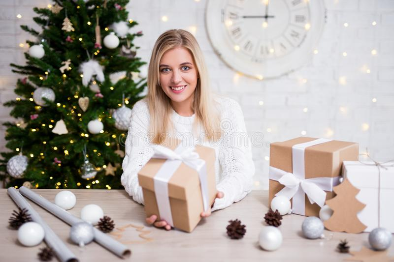 Young beautiful blond woman with Christmas gifts in living room stock photos