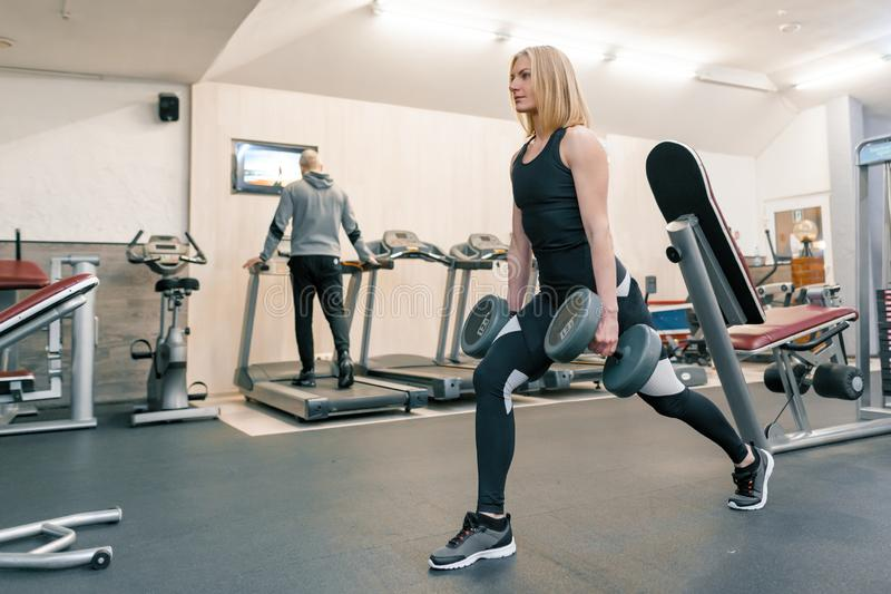 Young beautiful blond woman doing strength exercises with dumbbells in gym. Sport, fitness, bodybuilding, training, workout stock photo