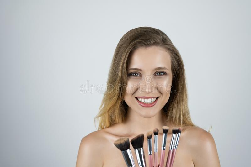 Young beautiful blond woman holding pink brushes isolated white background stock images