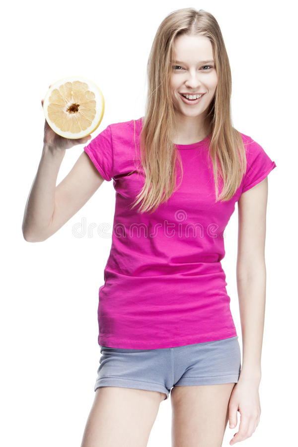 Young beautiful blond woman holding pomelo stock photography