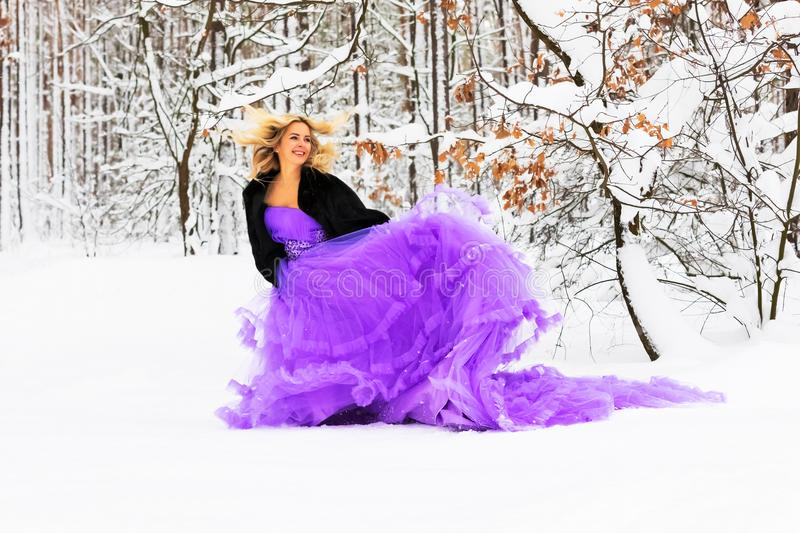 Young woman in a long dress in winter forest. Young beautiful blond woman in a long purple dress in the snowy winter forest or wood outdoors royalty free stock photos