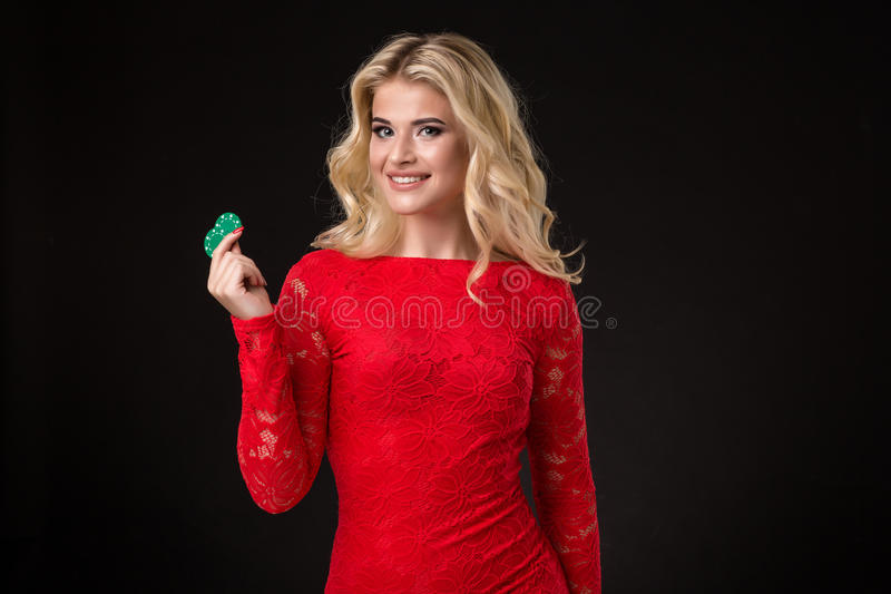 Young beautiful blond woman with poker chips over black. Poker stock image
