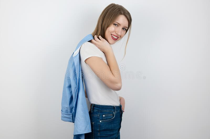 Young beautiful blond woman with a shirt on her shoulder poses professionally standing on isolated white background, modelling stock photo