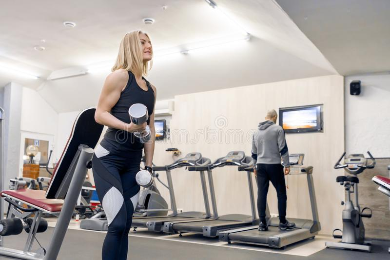 Young beautiful blond woman doing strength exercises with dumbbells in gym. Sport, fitness, bodybuilding, training, workout royalty free stock photos