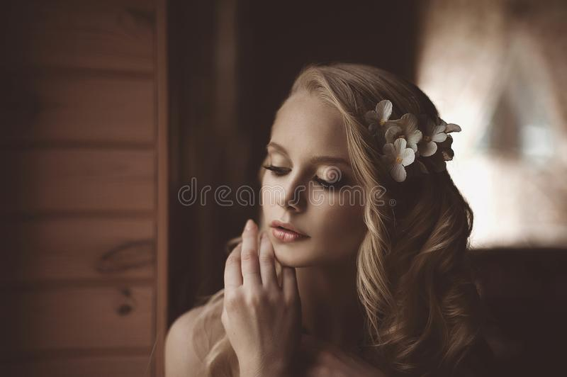 Young beautiful blonde in the bed at morning time near window under Sun rays with flower in the hair. Tender romantic mood royalty free stock photography