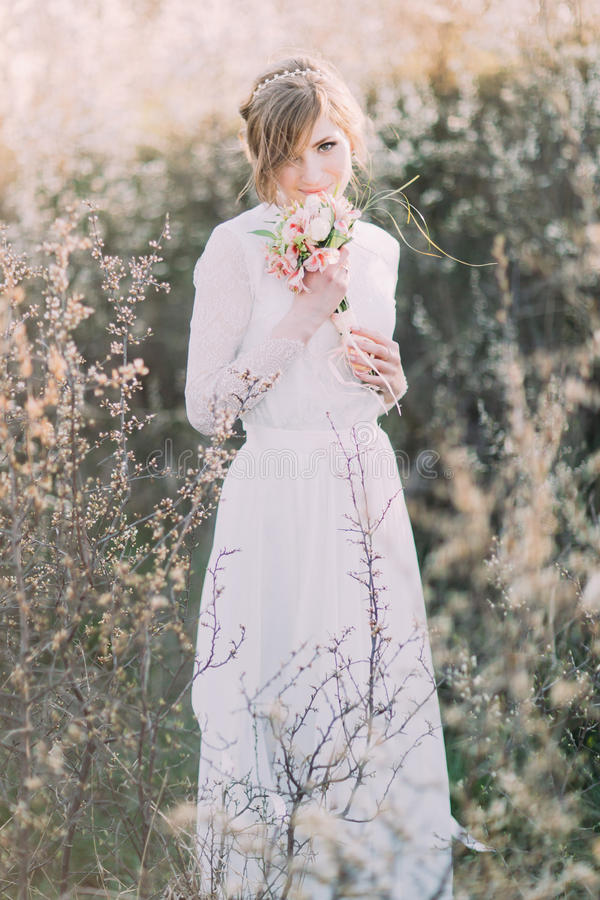 Young beautiful blonde bride wearing white dress with bouquet in blooming meadow. Delicate girl enjoys spring nature stock photos
