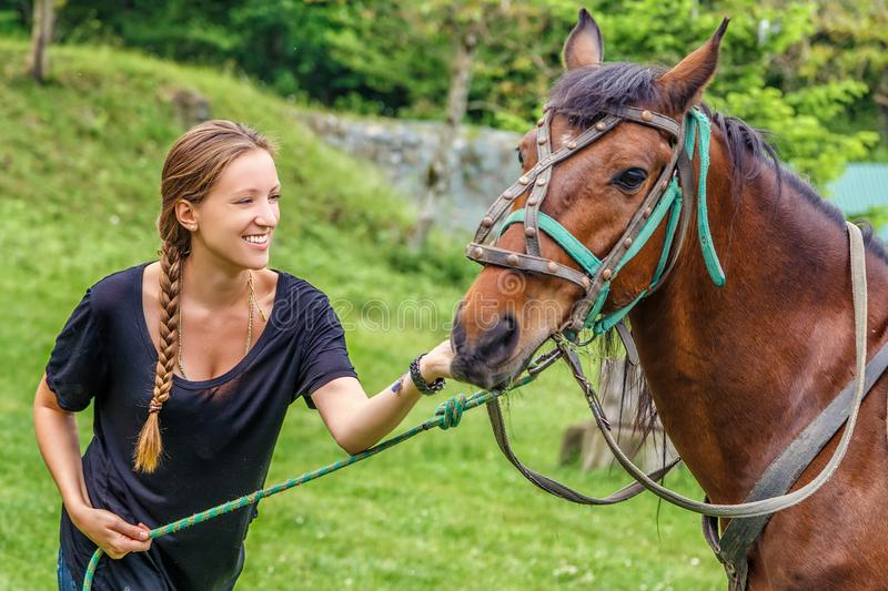 Young beautiful blonde Caucasian woman with long braid smiling and feeding brown horse holding it by harness at countryside on sum royalty free stock photos