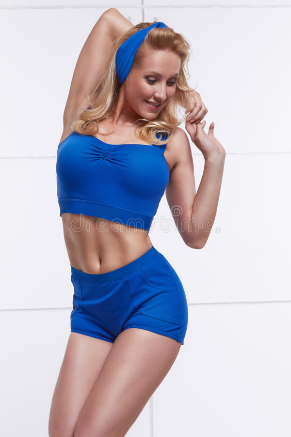 Young beautiful blonde dressed in style pinup blue halter top and young blonde dressed in style pinup blue halter top and shorts and headband beautiful figure tanned body fitness sport thecheapjerseys Gallery