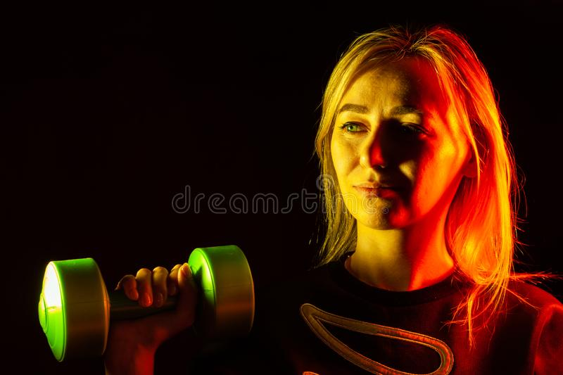 A young beautiful blonde girl in a black sweatshirt is holding a green plastic dumbbell in her hand raising up with backlight in royalty free stock photo