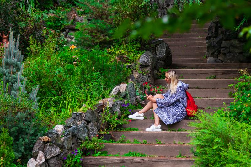 Young beautiful blonde girl in a blue raincoat sits on a wooden staircase with stone walls in a green flowered garden texting on stock image