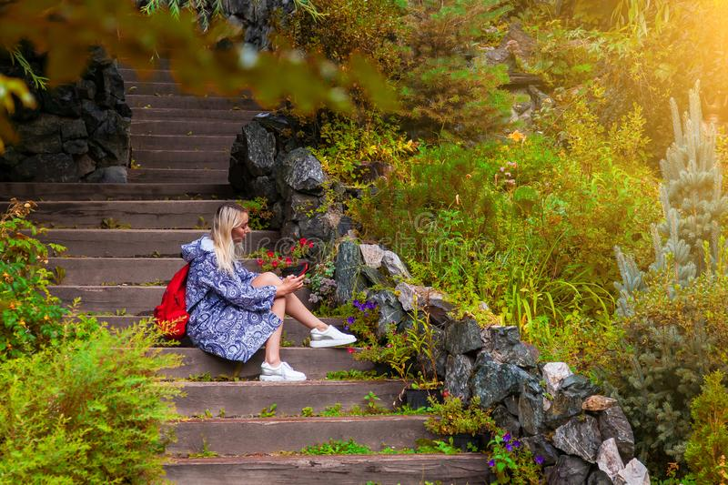 Young beautiful blonde girl in a blue raincoat sits on a wooden staircase with stone walls in a yellow autumn flowered garden royalty free stock photo