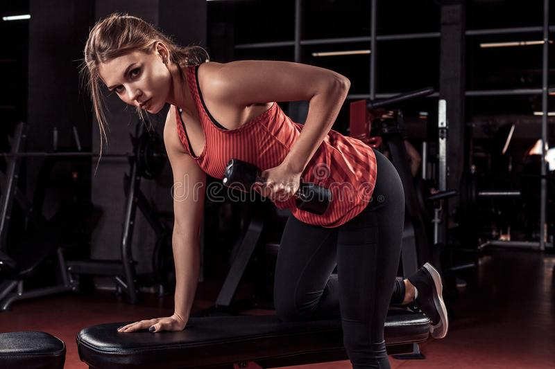 Young beautiful blonde girl is engaged in sports training with dumbbells in the gym royalty free stock photos