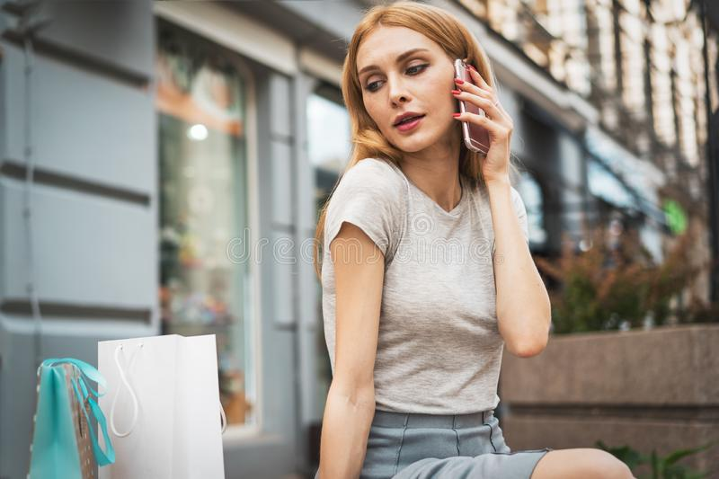 Young beautiful blonde girl with paper bags sitting at the shop window and talking on the phone stock photos