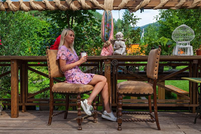 Young beautiful blonde girl in a pink dress sits with a cup of coffee in her hands in a cafe or restaurant in vintage style in royalty free stock image