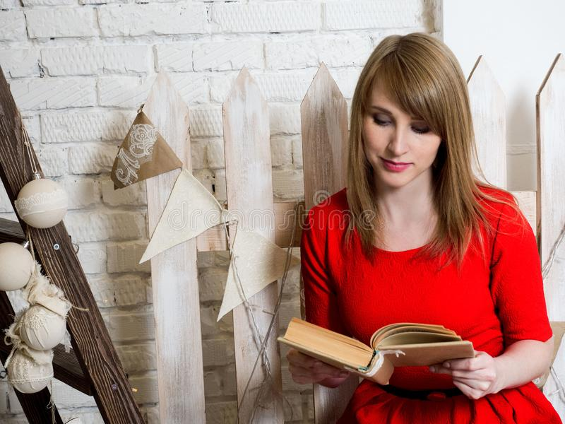 Young beautiful blonde girl in red dress is reading a book in a New Year`s interior. stock photos