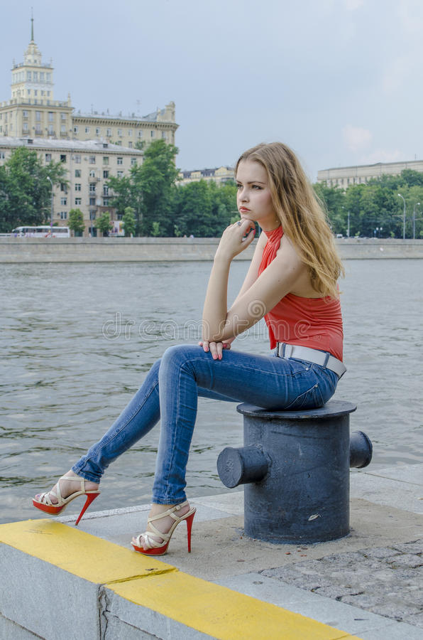 Download Young Beautiful Blonde Girl In A Red Summer Blouse And Jeans Posing Flexible Stock Photo - Image: 83700560