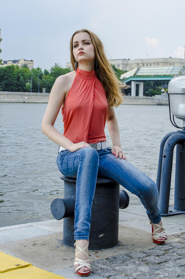 Download Young Beautiful Blonde Girl In A Red Summer Blouse And Jeans Posing Flexible Stock Image - Image: 83700581