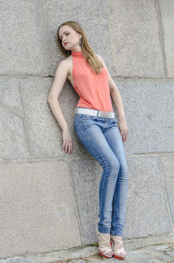 Download Young Beautiful Blonde Girl In A Red Summer Blouse And Jeans Posing Flexible Stock Photo - Image: 83700672