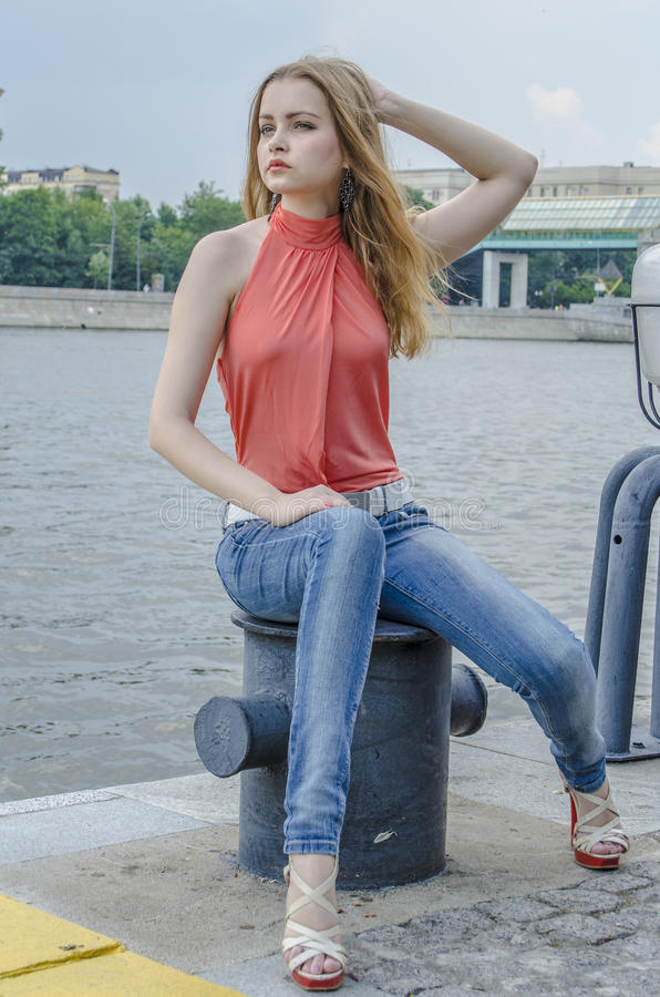 Download Young Beautiful Blonde Girl In A Red Summer Blouse And Jeans Posing Flexible Stock Photo - Image of beautiful, blouse: 83700790