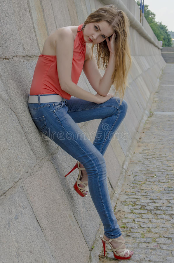 Download Young Beautiful Blonde Girl In A Red Summer Blouse And Jeans Posing Flexible Stock Image - Image: 83700795