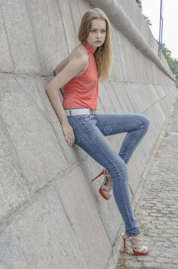Download Young Beautiful Blonde Girl In A Red Summer Blouse And Jeans Posing Flexible Stock Image - Image: 83700825