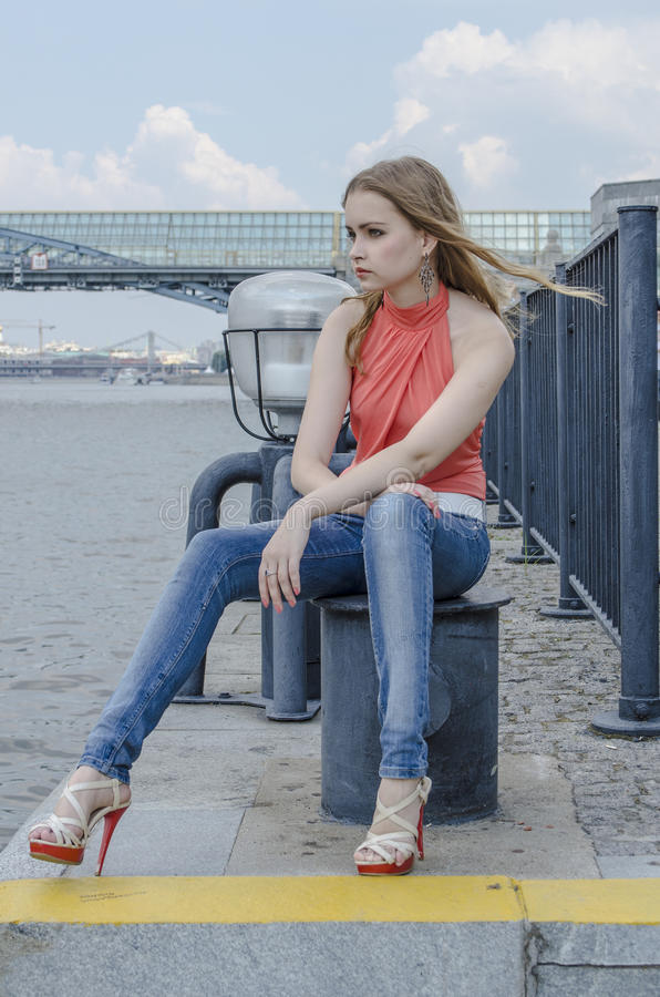 Download Young Beautiful Blonde Girl In A Red Summer Blouse And Jeans Posing Flexible Stock Photo - Image: 83700897