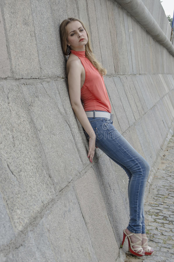 Download Young Beautiful Blonde Girl In A Red Summer Blouse And Jeans Posing Flexible Stock Image - Image: 83700949