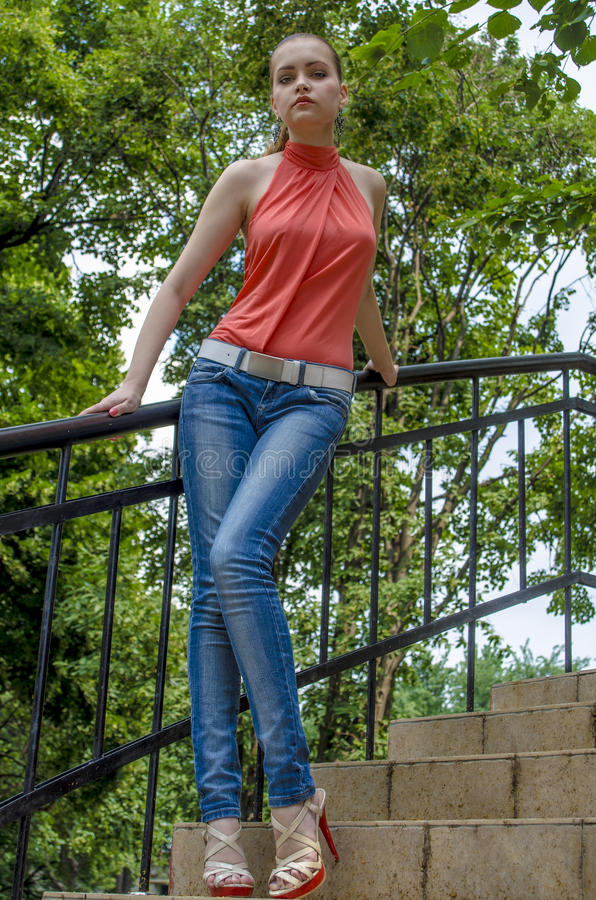 Download Young Beautiful Blonde Girl In A Red Summer Blouse And Jeans Posing Flexible Stock Photo - Image: 83701011