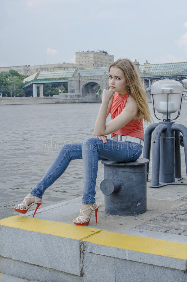 Download Young Beautiful Blonde Girl In A Red Summer Blouse And Jeans Posing Flexible Stock Image - Image: 83701501