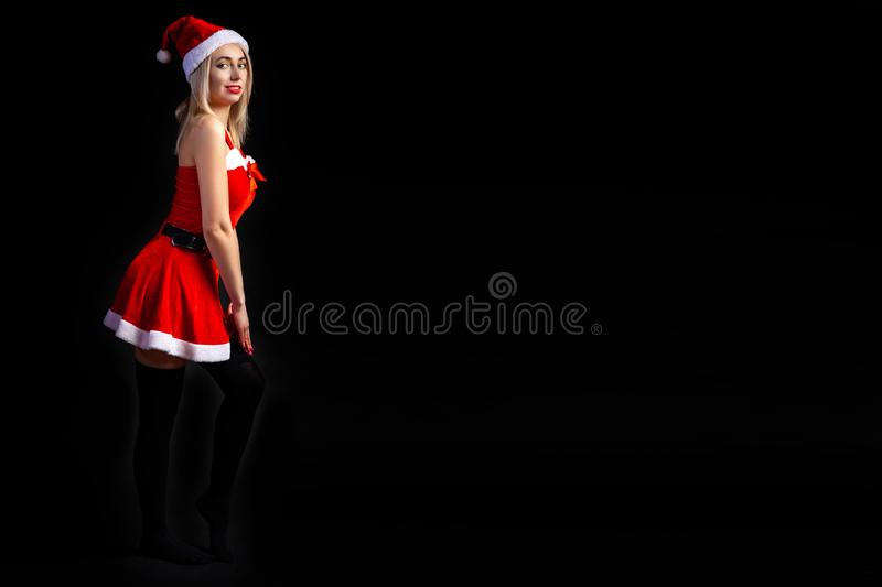 Young beautiful blonde girl in a sexy red Snow Maiden costume or Santa Claus on a black isolated background in the Christmas and stock image