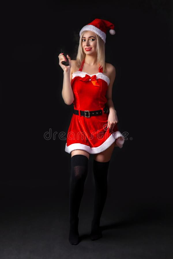 Young beautiful blonde girl in a sexy red Snow Maiden costume or Santa Claus with vape in hand on a black isolated background in royalty free stock photo
