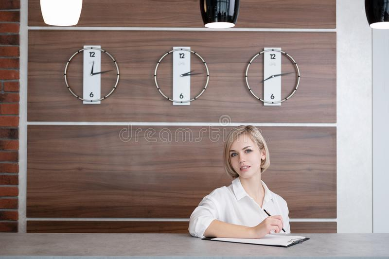 Young beautiful blonde girl with short hair in a white shirt. The receptionist at the reception desk at the hotel. stock image
