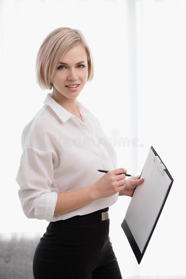 Young beautiful blonde girl with short hair in a white shirt is standing in the office and holding a notebook and pen. royalty free stock photo