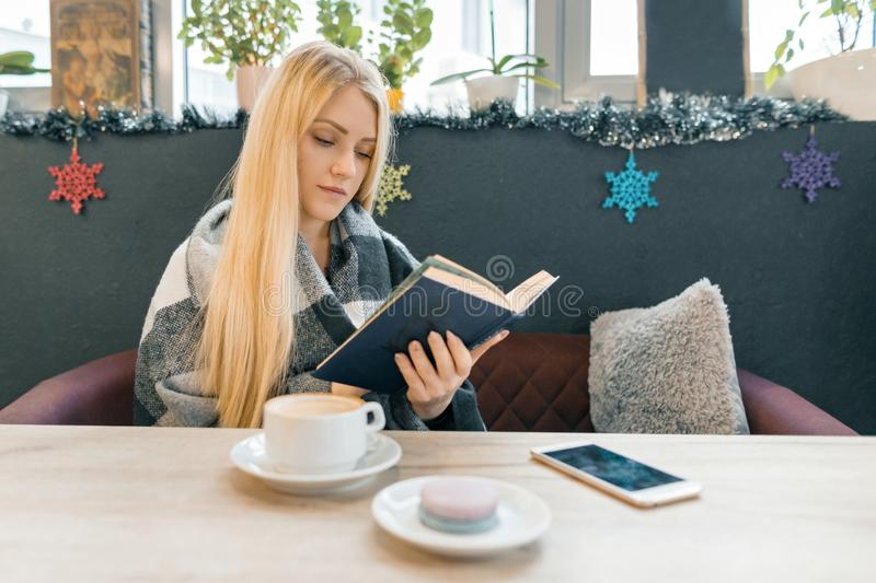 Young beautiful blonde girl sitting in coffee shop reading book stock photos