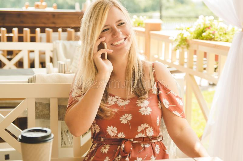 Young beautiful blonde girl in the summer in a cafe drinks coffee, talks on the phone and laughs.  royalty free stock photo