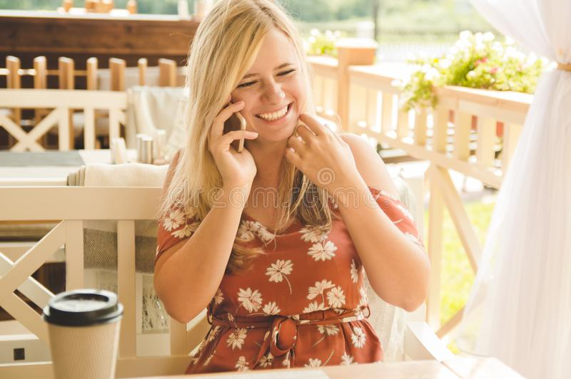 Young beautiful blonde girl in the summer in a cafe drinks coffee, talks on the phone and laughs.  stock images