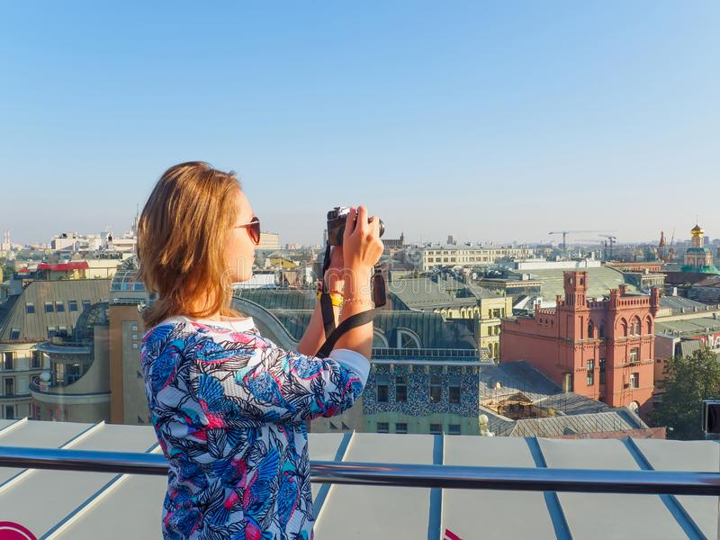Young beautiful blonde girl taking pictures of the city with a camera on a rooftop in Moscow, Russia. stock photography