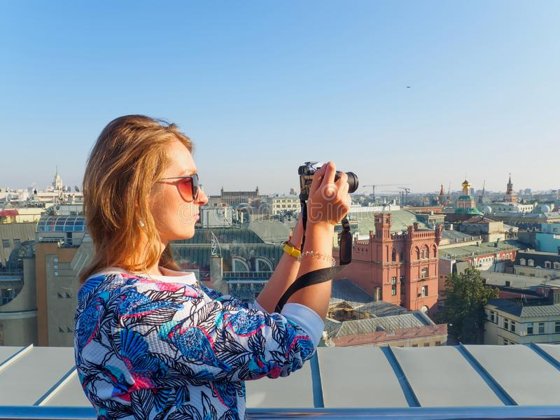 Young beautiful blonde girl taking pictures of the city with a camera on a rooftop in Moscow, Russia. royalty free stock images