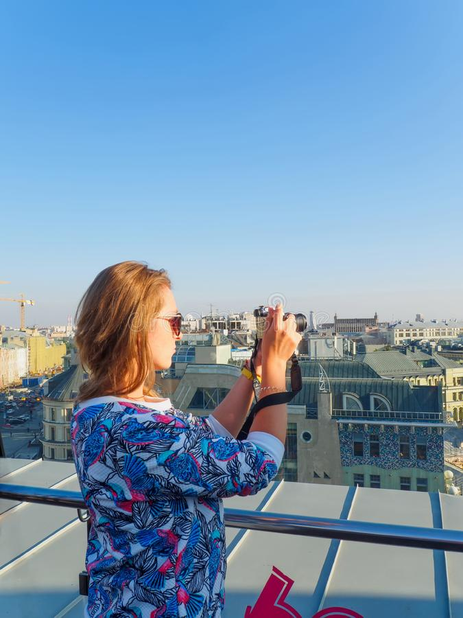 Young beautiful blonde girl taking pictures of the city with a camera on a rooftop in Moscow, Russia. stock photos