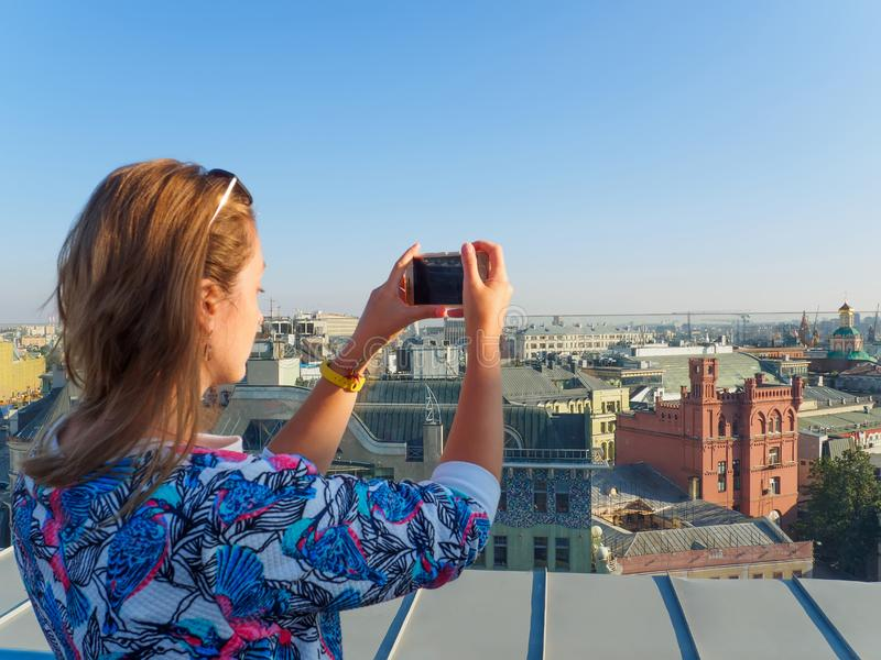 Young beautiful blonde girl taking pictures of the city with a smartphone on a rooftop in Moscow, Russia. stock photography