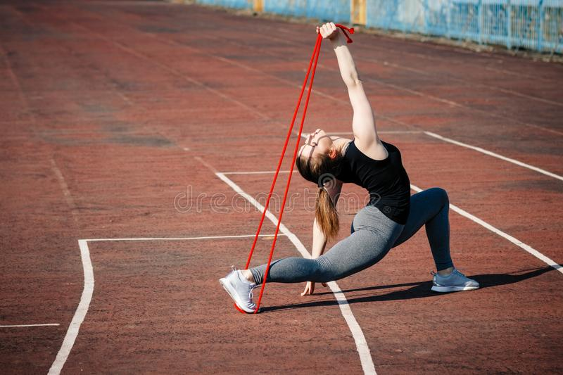 Young beautiful blonde hair sport girl doing exercises on running track of stadium. Tribunes on background. Summer women fitness royalty free stock images
