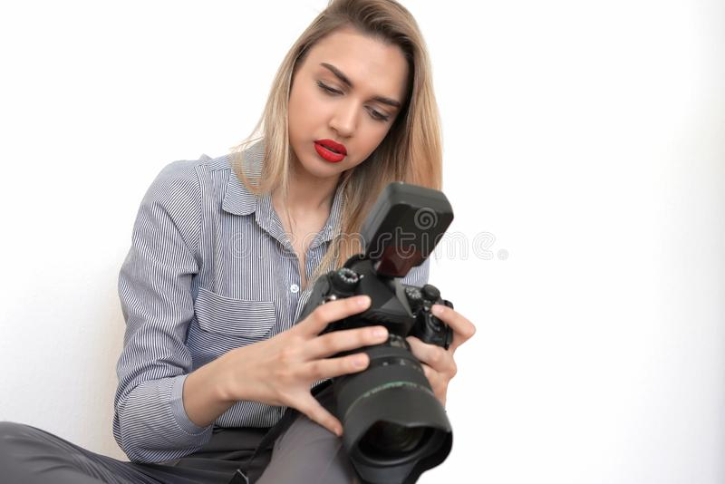 Young beautiful blonde looks at frames on a studio camera, white background stock photo