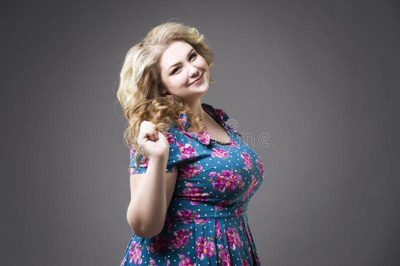 Young beautiful blonde plus size model in dres, xxl woman portrait on gray studio background royalty free stock photo