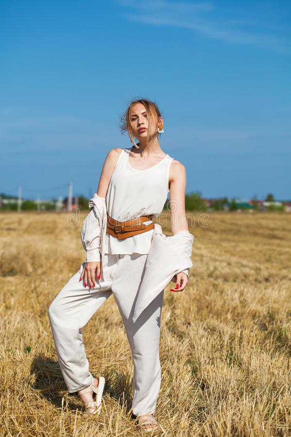 Young beautiful blonde woman in a beige suit posing against the background of a mowed wheat field royalty free stock photography