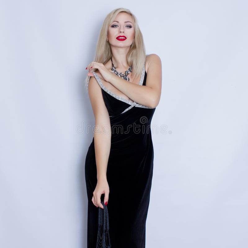 Young beautiful blonde woman in black evening dress. stock photo